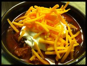 bowl of chili with cheese and sour cream