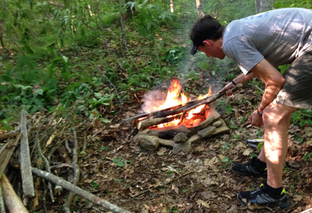 camper tending to a fire