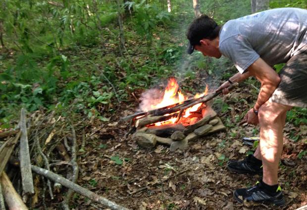 camper tending to a fire