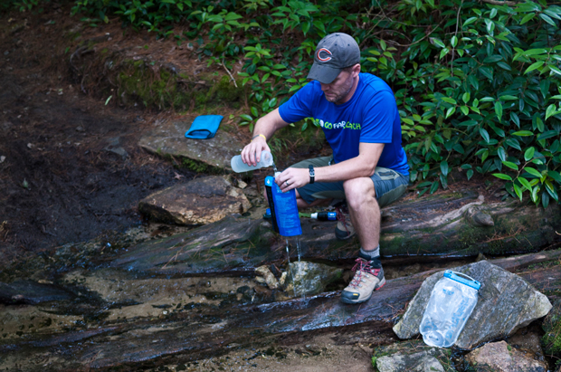hiker filtering water