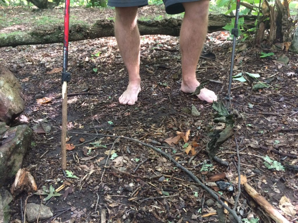barefoot man with broken trekking pole