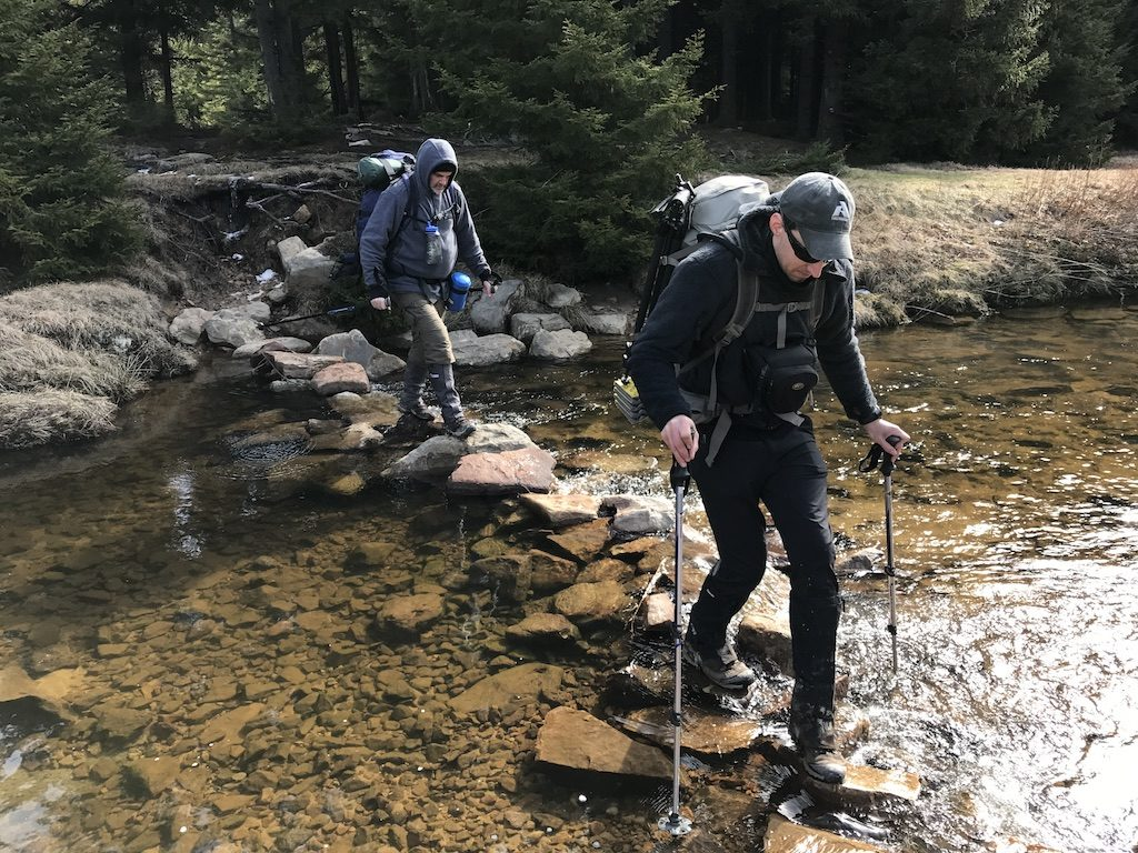 hikers crossing a creek