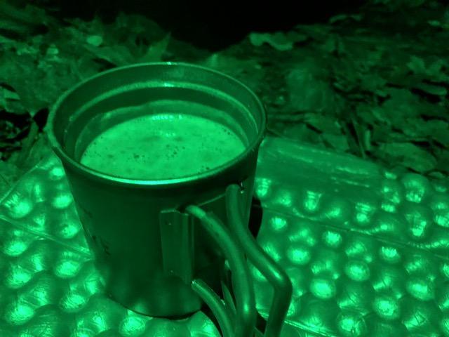 mug of hot cocoa illuminated by a green light